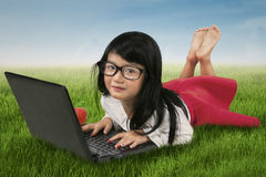Attractive child using laptop at the field Royalty Free Stock Images
