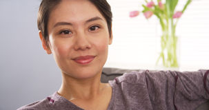 Attractive Chinese woman smiling on couch Royalty Free Stock Images