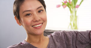 Attractive Chinese woman smiling on couch Royalty Free Stock Image