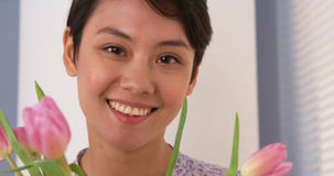 Attractive Chinese woman smiling with tulips Stock Photo