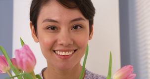 Attractive Chinese woman smiling with tulips Stock Photography