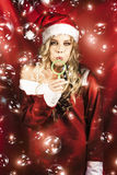 Attractive Christmas Woman Blowing Magic Bubbles royalty free stock photo