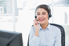 Attractive classy brown haired operator answering a call Stock Images