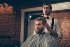 Attractive classy dressed barber shop hairdresser is turning client`s head to present his work for him. Stunning! Hairdo looks tr stock images