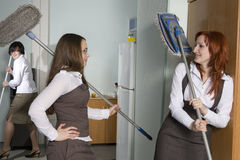 Attractive clerks washing the floor in office. Royalty Free Stock Photo