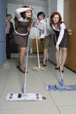 Attractive clerks washing the floor in office Stock Photo