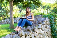 Attractive college student smiling in park with book Stock Photography