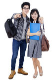 Attractive college students pointing at camera. Happy trendy college students with bags and books, posing together, pointing at camera Royalty Free Stock Images