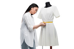 Attractive concentrated asian tailor measuring stylish white dress on dummy. Isolated on white Stock Photo