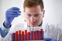 Attractive chemist holding pipette and working at laboratory. Attractive concentrated chemist holding pipette and working at laboratory Royalty Free Stock Image