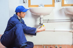 Attractive concentrating plumber repairing sink Royalty Free Stock Photography