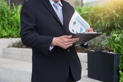 Attractive Confident businessman standing in a black suit and ho. Lding clipboard to analyze report of new financial project plan and checking account growing Royalty Free Stock Image