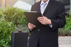Attractive Confident businessman standing in a black suit and ho. Lding clipboard to analyze report of new financial project plan and checking account growing Royalty Free Stock Images