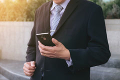 Attractive Confident businessman standing in a black suit and us. Ing smart phone to analyze investment Royalty Free Stock Images