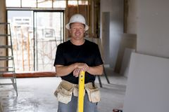 Attractive and confident constructor carpenter or builder man with protective hat posing happy working in industrial construction Stock Photo