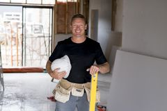 Attractive and confident constructor carpenter or builder man with protective helmet posing happy working at industrial constructi Stock Photos