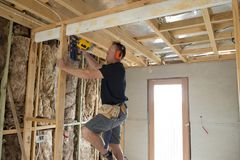 Attractive and confident constructor carpenter or builder man working wood with electric drill at industrial construction site stock images