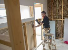 Attractive and confident constructor carpenter or builder man working wood with electric drill at industrial construction site. In installation and renovation Stock Image