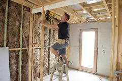 Attractive and confident constructor carpenter or builder man working wood with electric drill at industrial construction site. In installation and renovation stock photo
