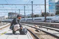 Attractive confident hispanic man having a backpack front of him with a clothes bag, walking beside a platform at train. Station stock photo