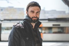 Attractive confident mature man with beard on blurred background. Fashionable cool male dressed in stylish clothes Royalty Free Stock Image