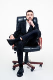 Attractive confident young bearded businessman sitting in  office chair Stock Photos