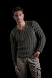 Attractive and confident young man wearing knitted sweater. Smiling, isolated on black Stock Photos