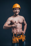 Attractive construction worker. Young confident man gesturing and looking at camera while standing against black background Royalty Free Stock Photography