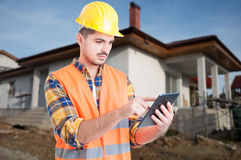 Attractive constructor working on modern tablet. Outside in front of renovated house Stock Images