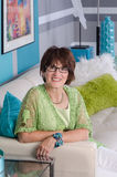 Attractive contemporary senior woman on sofa. Portrait of a contemporary woman sitting on a sofa in her beautifully decorated home Royalty Free Stock Photos