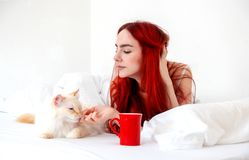 Attractive, contented, young, sexy red-haired woman lying relaxed in bed with her cat with her coffee in a red cup, copy space. Attractive, contented, young royalty free stock photo