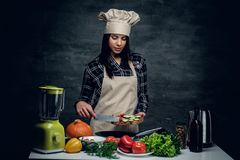 Attractive cook female cutting vegetables. Attractive cook female cutting vegetables for a healthy salad royalty free stock images