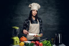 Attractive cook female cutting vegetables. Attractive cook female cutting vegetables for a healthy salad royalty free stock image