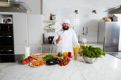 Attractive cook  smiling happystanding on light big kitchen Stock Photo