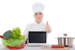 Attractive cook woman in uniform sitting at the kitchen and lapt Stock Photo