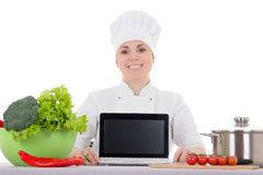 Attractive cook woman in uniform sitting at the kitchen and lapt Royalty Free Stock Photo