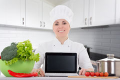 Attractive cook woman in uniform sitting in the kitchen and show. Cooking and blogging concept - attractive cook woman in uniform sitting in the kitchen and Stock Images