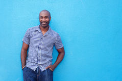 Attractive cool african guy. Portrait of an attractive cool african guy standing against a blue wall Royalty Free Stock Photo