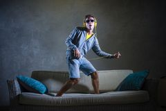 Attractive and cool happy man playing air guitar listening to music with yellow headphones holding mobile phone jumped on top of. Young attractive and cool happy Royalty Free Stock Images