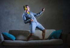 Attractive and cool happy man playing air guitar listening to music with yellow headphones holding mobile phone jumped on top of. Young attractive and cool happy Stock Image