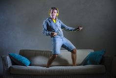 Attractive and cool happy man playing air guitar listening to music with yellow headphones holding mobile phone jumped on top of. Young attractive and cool happy Royalty Free Stock Photography