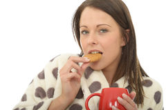 Attractive Cosy Relaxed Happy Young Woman Eating a Biscuit with Tea Stock Images