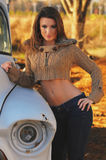 Attractive country girl. Tan country girl in short brown sweater and blue jeans, old white truck and field in background Royalty Free Stock Photo