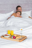 Attractive couple asleep with breakfast tray on bed Stock Photography