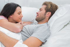 Attractive couple awaking and looking at each other Stock Images