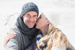 Attractive couple on the beach in warm clothing Stock Image