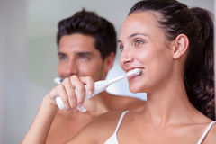 Attractive couple brushing their teeth in the morning Stock Photos
