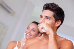 Attractive couple brushing their teeth in the morning Royalty Free Stock Photo