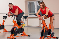 Attractive couple bycicle cycling in gym Stock Photo