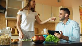 Attractive couple chatting in the kitchen early morning. Beautiful woman feed her husband while cooking breakfast Royalty Free Stock Image